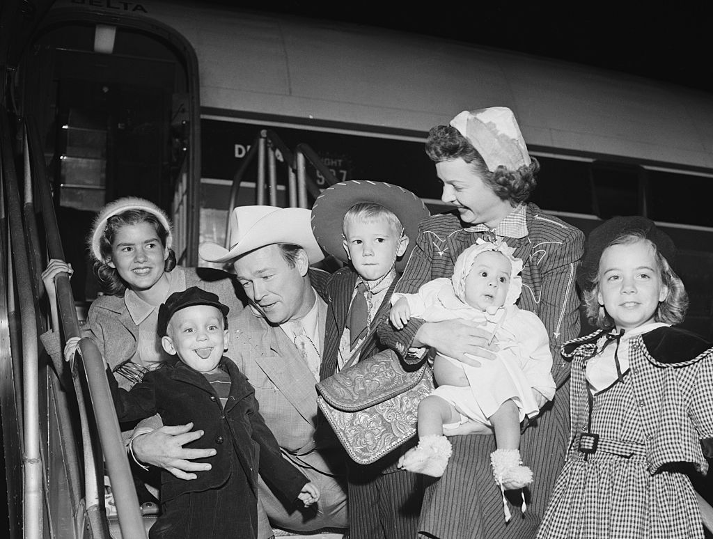 Roy Rogers and actress wife Dale Evans arrive by plane in Los Angeles, Bringing with them two newly adopted children, five year old Sandy and five-month old Doe.