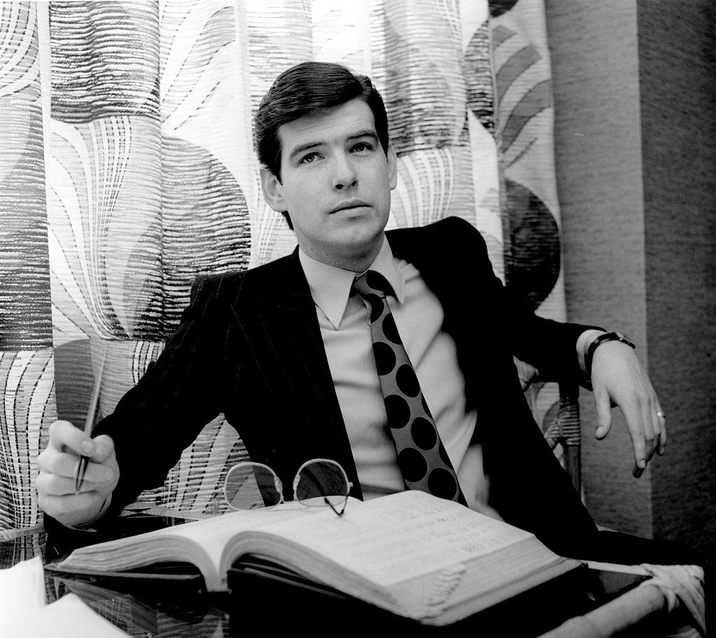 Portrait of Irish actor Pierce Brosnan sitting behind an office desk dressed in a suit and tie,