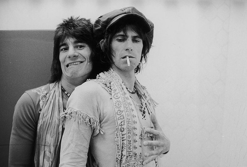 Ronnie Wood wraps stands behind Keith Richards and wraps an arm around him, while Keith holds a cigarette in his mouth and looks down.