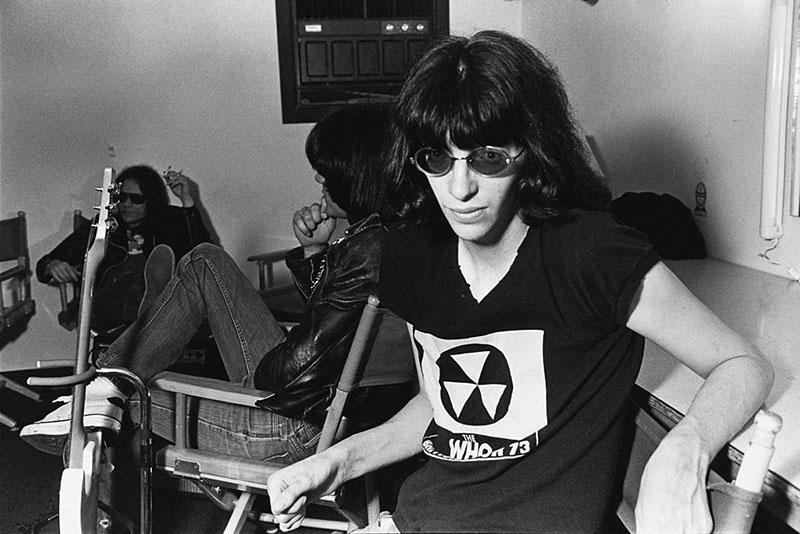 The Ramones sit on a couch calmly waiting to perform.