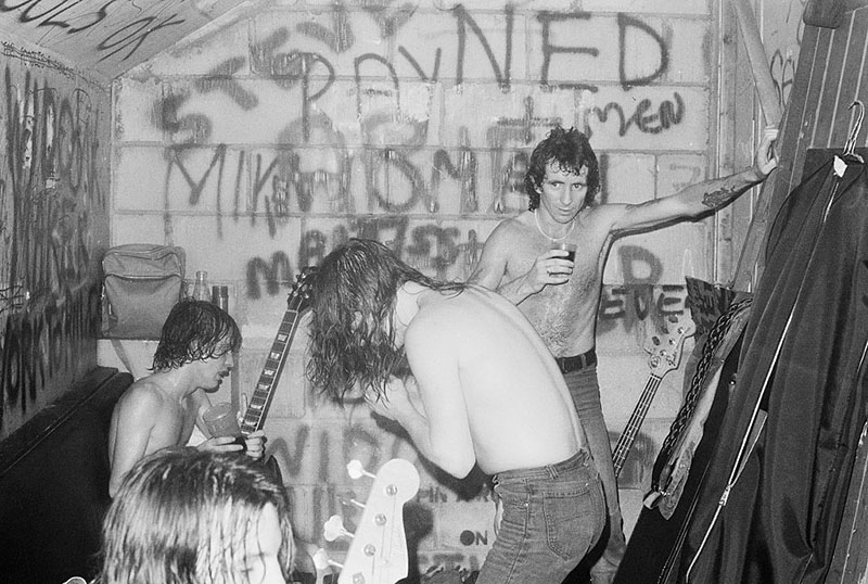 Band members unwind in a graffiti-riddled room with sweat locks and tired expressions.