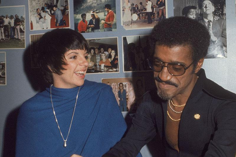 Sammy Davis smokes a cigarette while chatting with Liza Minelli in his dressing room, the walls of which are adorn with photos of Sammy throughout his career.