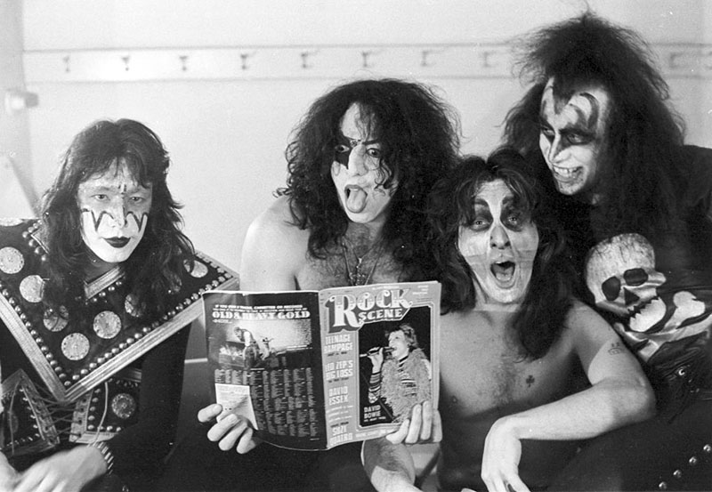 The members of Kiss sit cozy together in the dressing room while look into a magazine.