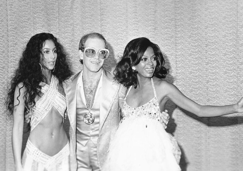 Cher, Elton John, and Diana Ross seem distracted by something to their left while posing for a group photo.