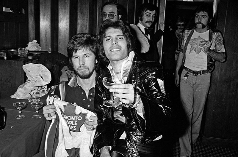 Freddie Mercury sits on his bandmate's lap while cheersing the camera with his martini glass.