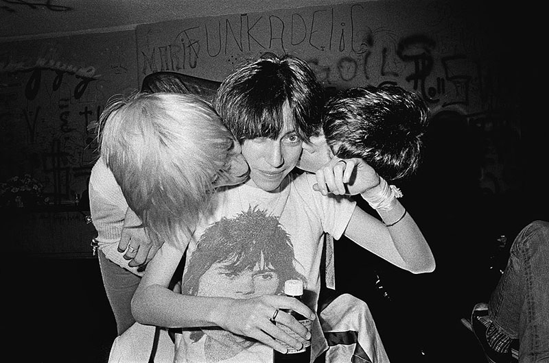 Patti Smith sits in the Whiskey A Go Go while two musicians lean down to kiss each of her cheeks.