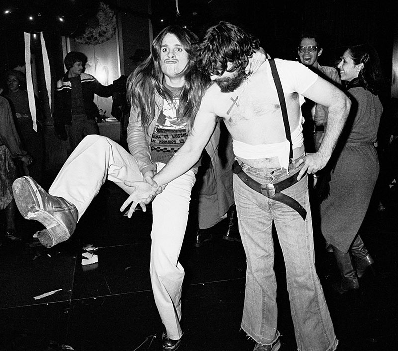 Ozzy Osbourne makes a duck face while kicking up one of his legs and gripping onto his band mate.