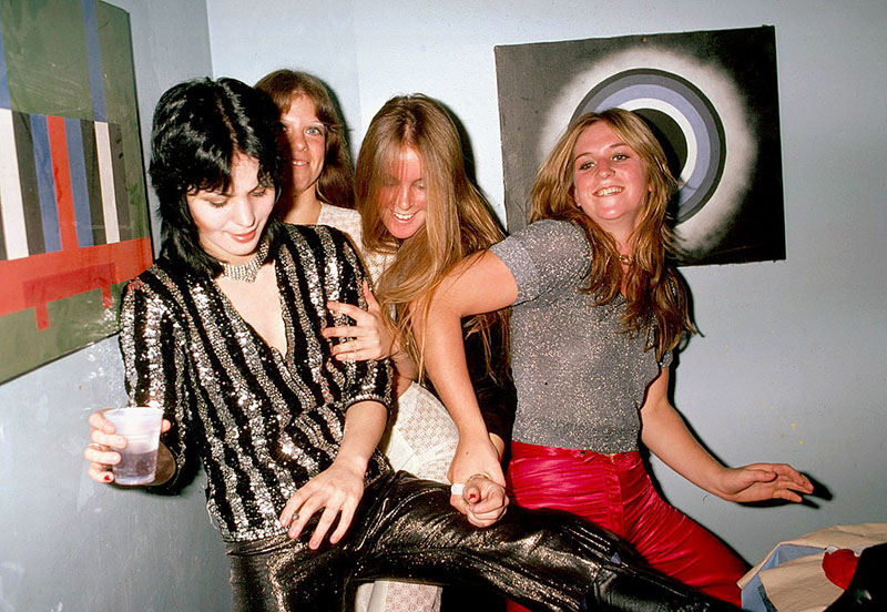 Four members of the runaways fall into one another while smiling backstage.