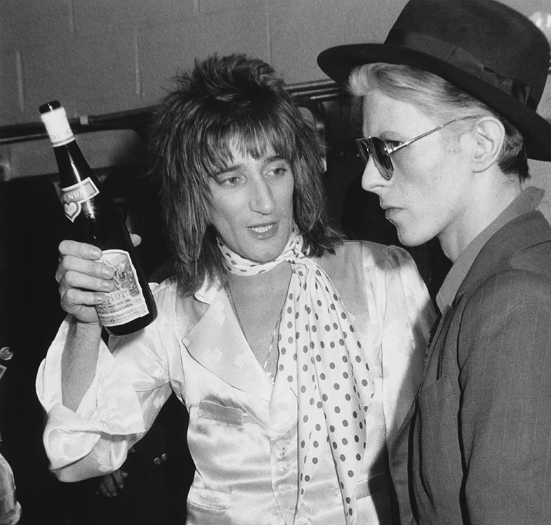 Rod Stewart hold up a bottle of wine while talking to Daivd Bowie, who looks rather ominous with his sunglasses and straightface