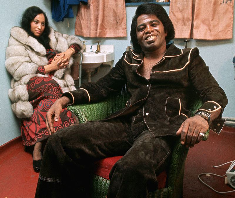 James Brown wears a brown suade suit and leans back in his armchair backstage, smiling to the camera.