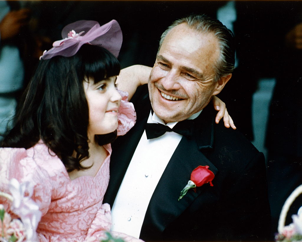 marlon brando smiling and wearing a black dinner suit with a white shirt, with wing-tip collars, and a black bow tie,
