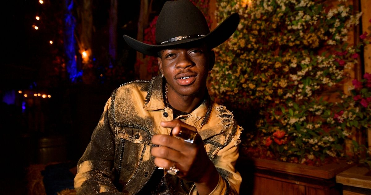 Lil Nas X points to the camera wearing a cowboy hat