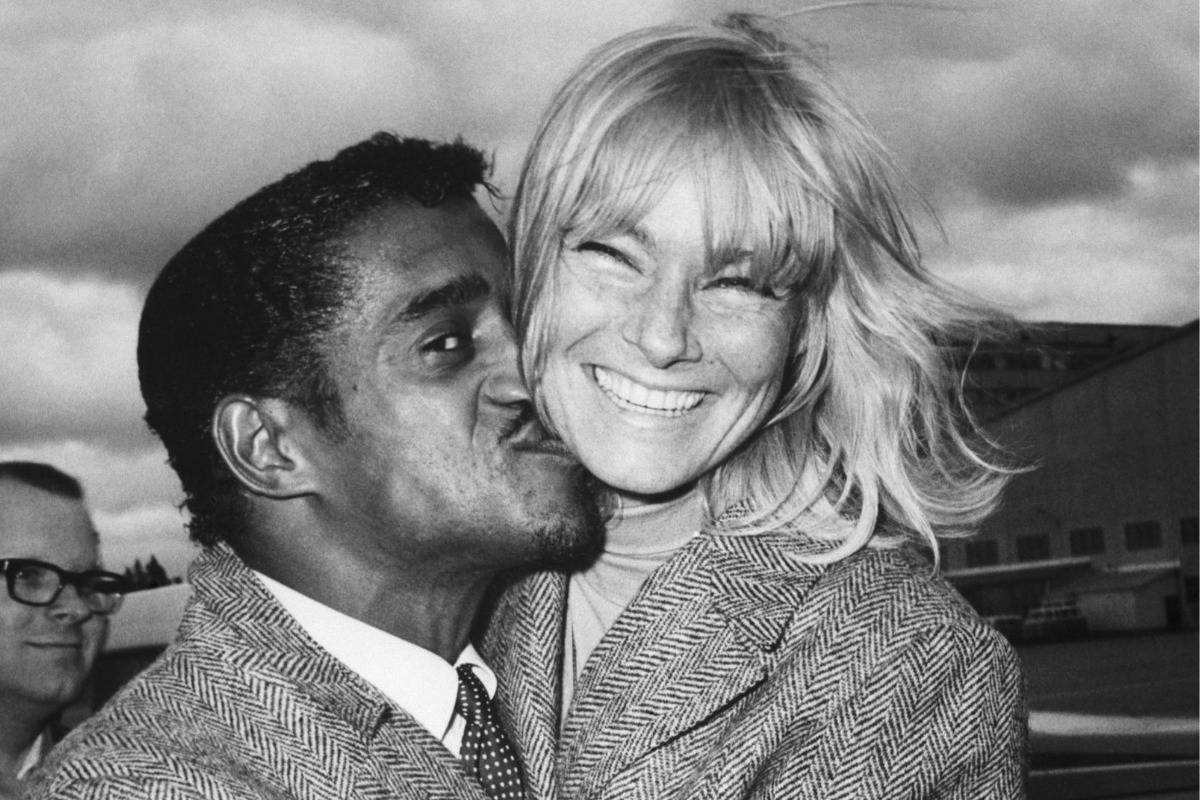 Sammy Davis Jr. kisses his Swedish wife May Britt